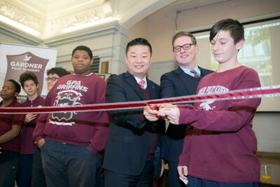 Superintendent of Boston Public Schools Tommy Chang (center), Vice President of Harvard Public Affairs and Communications Paul Andrew, and Gardner Pilot Academy student Artur Shehu cut the ribbon to open a new science classroom at GPA that was seeded with a donation from Harvard.