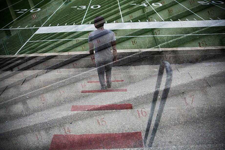 A solitary runner gazes across Harvard Stadium as he climbs and descends the steps.
