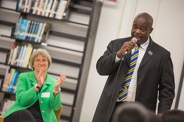 Harvard President Drew Faust applauds Principal Wallace Aristide of Miami Northwestern High School during her visit to Florida to speak about pursuing higher education.