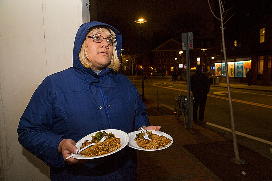 Eva D. stands outside the Y2Y homeless shelter with two meals she was given by shelter staff. Her 30-day eligibility is up and she cannot come inside this evening. She will give one meal to a friend who is waiting down the street, then try to find another shelter where she can spend the night.