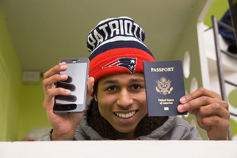Michael displays his two most prized possessions, his phone and passport. Michael traveled to France recently to visit his aunt, who lives in Nice and paid his way. Michael is an avid Patriots fan, and recounts past playoff games with great passion, acting out plays by quarterback Tom Brady.