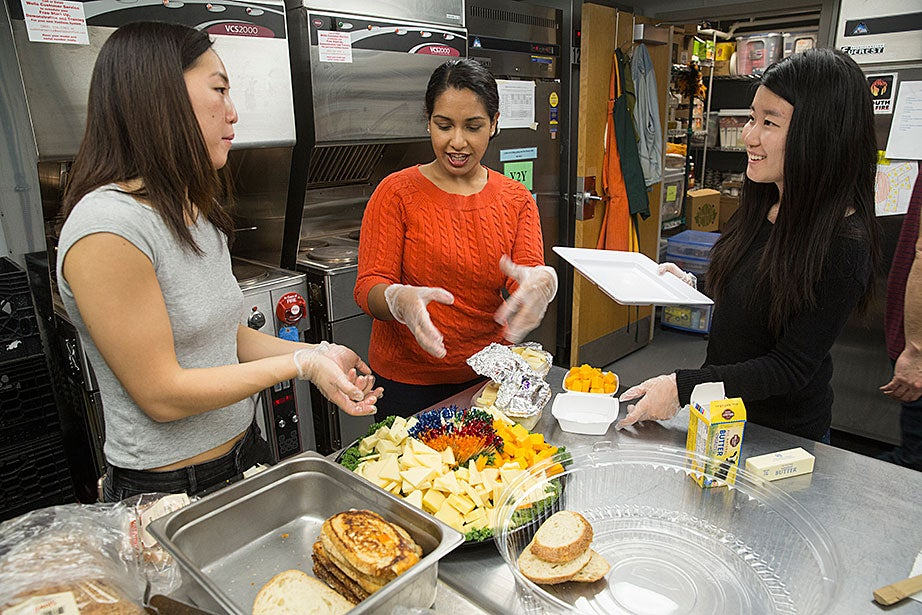 Julie Park '17 (from left), Jina John '17 of Harvard Law School, and Sue Wang '17 confer while preparing dinner. Local restaurants donate much of the food. Some is simply reheated, or in the case of sandwiches, served cold, but students also get creative with pasta, rice, and vegetable dishes that provide healthy alternatives to ready-made meals.