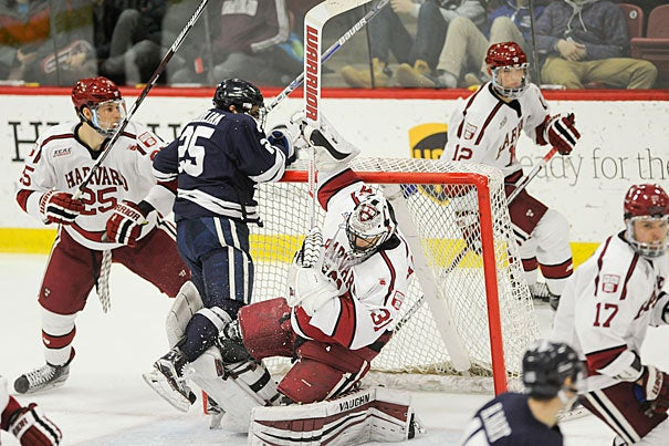 Crimson goalie Merrick Madsen '18 is upended by Yale's Chris Izmirlian. Harvard went on to win Friday's game 6-4. On Saturday, Harvard and Yale met again on the ice, with the Crimson beating Yale 4-3. Jon Chase/Harvard Staff Photographer