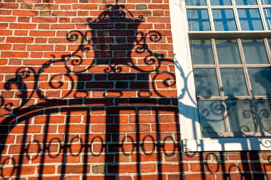 The Class of 1874 Gate, Northwest, casts a shadow on the brick wall of Lionel Hall. The ironwork masterfully joins C- and S-shaped scrollwork.