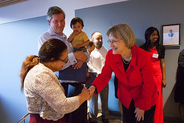 "New U.S. citizen Ana Umana (left) is congratulated by President Drew Faust. Lars Madsen, (center) became a U.S. citizen last year. Both he and Faust spoke during the Harvard Bridge Program's Annual Citizenship Celebration Dinner. ""[R]emember how precious your citizenship really is, and use it,"" said Faust. ""Take up not just its privileges, but also its responsibilities."""