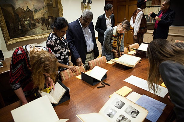 "Writers from Harvard's Scholars at Risk Program toured a selection of books and literary artifacts at Houghton Library prior to a panel discussion. The ephemera included the handwritten manuscript copy of the poem ""Annabel Lee"" by Edgar Allen Poe and a fragment of Arabic script on papyrus from 600 B.C."