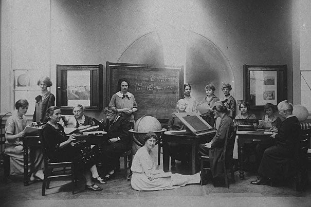 Margaret Harwood sat on the floor for this posed tableau on May 19, 1925. Harvia Wilson is at far left, sharing a table with Annie Cannon (too busy to look up) and Antonia Maury (left foreground). The woman at the drafting table is Cecilia Payne.""