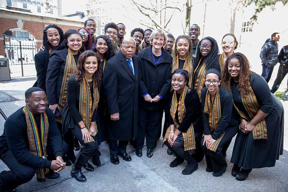 """Unveiling a plaque to honor four enslaved people who lived and worked at Wadsworth House—Titus, Venus, Bilhah, and Juba—U.S. Rep. John Lewis and President Faust are pictured here in April 2016 with the Harvard Kuumba Singers. """"The past never dies or disappears"""" Faust wrote in a Harvard Crimson Op-Ed published in advance of the unveiling. """"It continues to shape us in ways we should not try to erase or ignore. In more fully acknowledging our history, Harvard must do its part to undermine the legacies of race and slavery that continue to divide our nation."""" Rose Lincoln/Harvard Staff Photographer"""