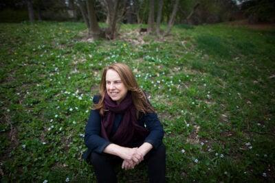 Pamela Silver sitting in a field.
