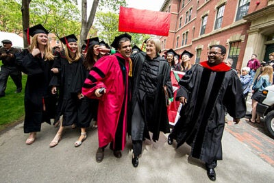 Late arrival Dean Rakesh Khurana (from left) greets Harvard President Drew Faust and  the Rev. Professor Jonathan Walton as they lead graduating seniors through Harvard Yard to  the Baccalaureate Service in the Memorial Church.