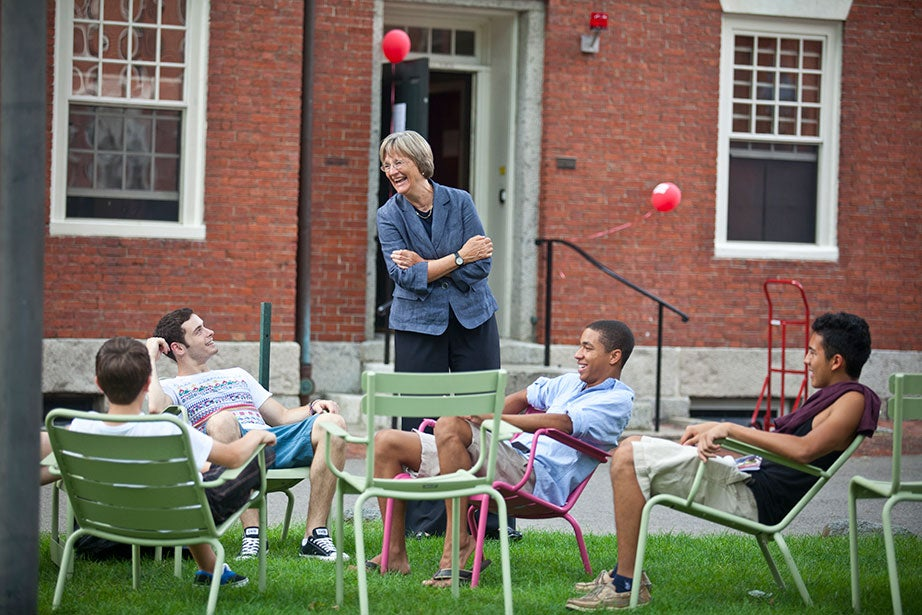 """As the class of 2015 moves into Harvard Yard, President Faust speaks with students in the colorful Luxembourg Chairs. The chairs are a key component of Faust's Common Spaces initiative, which she called """"an effort to create new spaces that will draw our increasingly diverse and interdisciplinary community together and enhance the intellectual, social, and cultural life that is at the core of the Harvard experience."""" Photo by Justin Ide"""