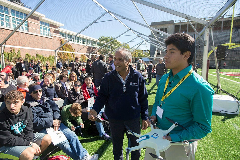 """During """"Making Robotics Fly,"""" an event at Harvard Stadium that was part of the Boston-wide ideas festival HUBweek in the fall of 2015, John Aleman of the drone company CyPhY leads a demonstration for Krishna Palepu (left), the Ross Graham Walker Professor of Business Administration. The University anticipates deep and broad collaboration in engineering and entrepreneurship from a growing partnership between HBS and SEAS. Kris Snibbe/Harvard Staff Photographer"""
