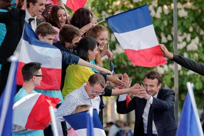 French President-elect Emmanuel Macron (right) greets supporters ahead of his landslide victory over far-right populist Marine Le Pen. Despite his margin of victory, Gunzberg Center senior affiliate Arthur Goldhammer predicts Macron will have little time to enjoy his political capital.