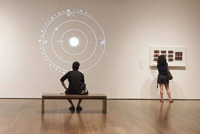 "A Harvard Art Museums visitor takes in the projections of the magic lantern in the ""Philosophy Chamber"" exhibit."