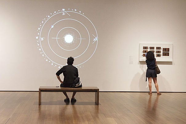 """A Harvard Art Museums visitor takes in the projections of the magic lantern in the """"Philosophy Chamber"""" exhibit."""