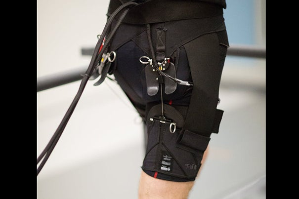 A system of actuation wires attached to the back of the exosuit provides assistive force to the hip joint during running.