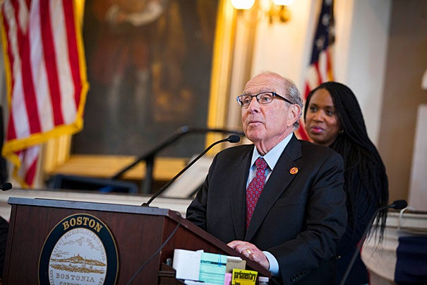 To honor its 150th anniversary, the Boston City Council recognizes Harvard School of Dental Medicine at Faneuil Hall. Dean R. Bruce Donoff (standing) addresses the council, while Councilor Ayanna Pressley looks on. The School is hosting an open house today.