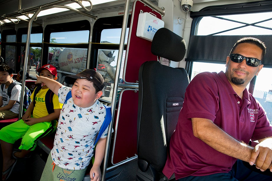 Kevin Nguyen, 9, says goodbye to his mother after boarding the Harvard shuttle. Dennis Pena is at the wheel.