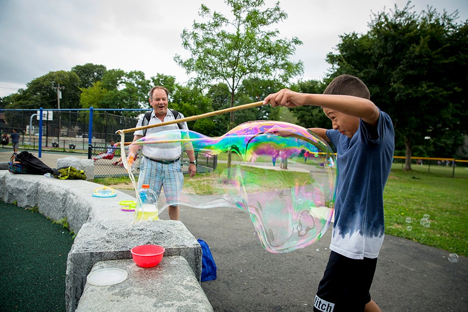 Jeffrey Peilco, 8, makes sure not to get wet while using a bubble kit that Kerry McGowan (left), Phillips Brooks House Association program director, made for the campers.