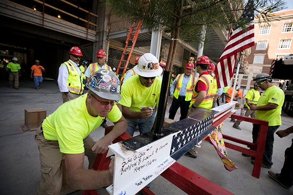 Construction workers sign a beam during the topping-off ceremony at the Richard A. and Susan F. Smith Campus Center that marked the halfway point of the Center's renovations.