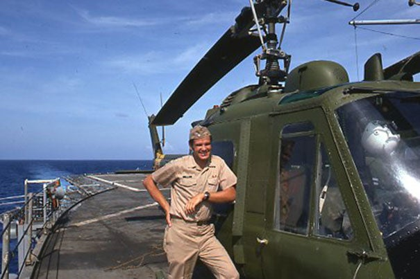 Bertram Zarins poses in front of a helicopter on board the USS Okinawa.