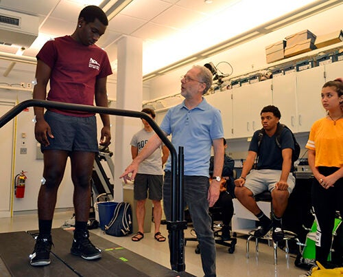 Cambridge-Harvard Summer Academy student Simão Silva (left) gets running tips from Harvard Professor Daniel Lieberman.