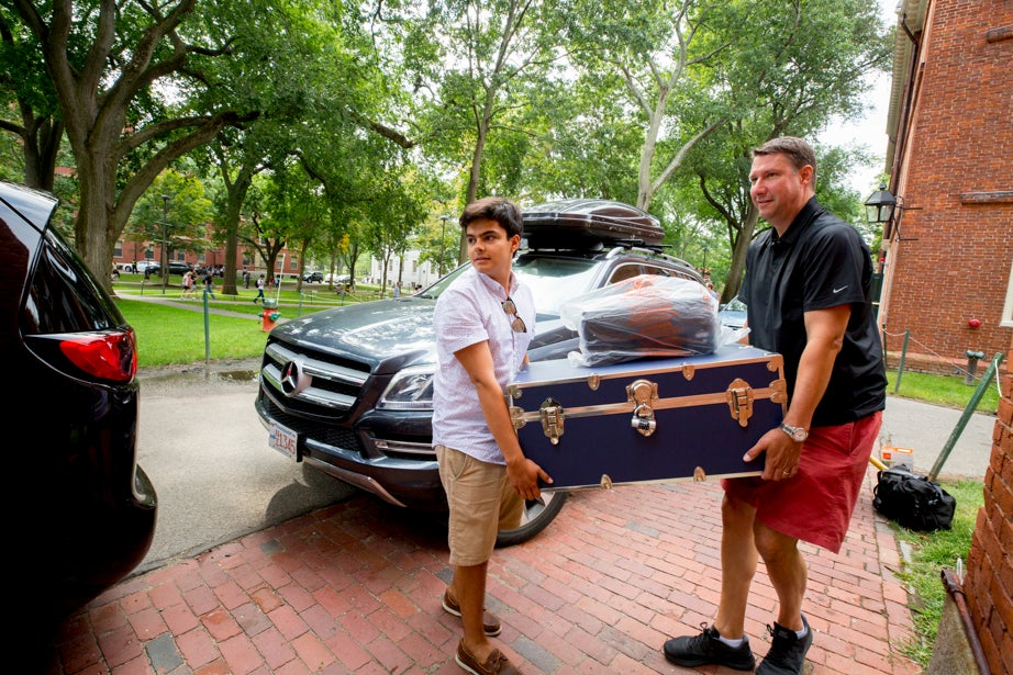 Fernando Young '21 has help from his dad, Chris, moving into his Stoughton Hall room from Nantucket. Rose Lincoln/Harvard Staff Photographer