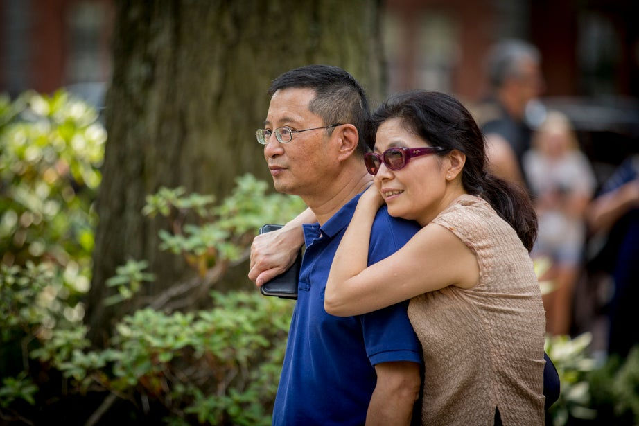 Jeff and Ling Li watch as their daughter, Katelyn '21, says goodbye to the friends she made hiking in the woods with the Freshman Outdoors Program. Rose Lincoln/Harvard Staff Photographer
