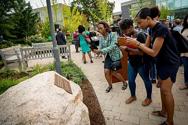 Students and faculty snap photos of a new plaque on the Law School campus that honors the slaves of the Royall family, whose scion, Isaac Jr., helped finance the School's establishment in 1817.
