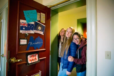 Roommates Kristie Colton (from left), Georgia Seidel, and Rebecca Chen peak inside their room in Thayer Hall.