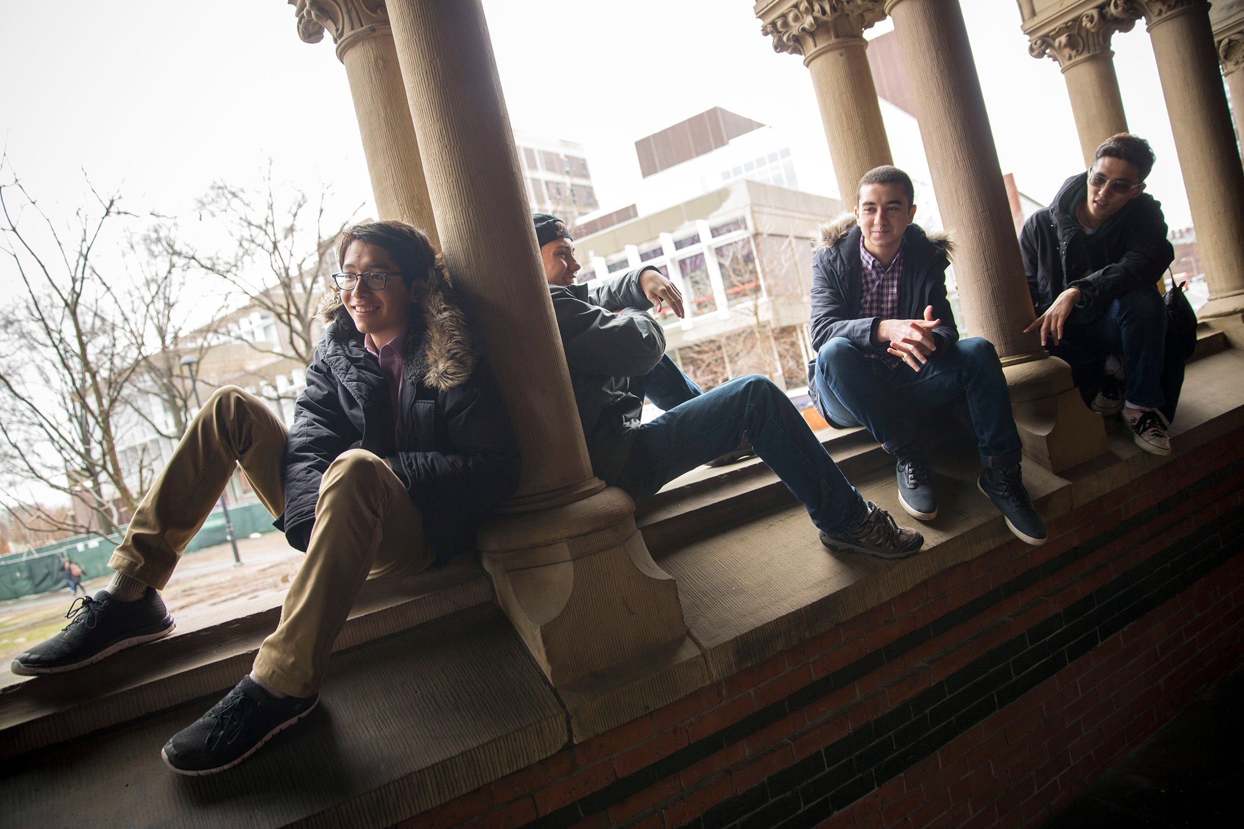 "Roommates, Kenneth Shinozuka, (from left to right) and Clifford ""Scotty"" Courvoisier, Abdelrhman ""Abdul"" Saleh, Sung Ahn, All class of '20 who live in Holworthy Hall together, talk outside Annenberg Hall with the Science Center in the background."