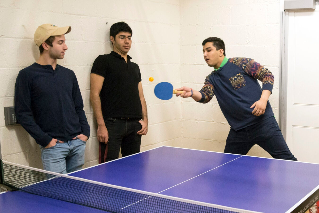 Roommates in Wigglesworth around ping pong table: (l to r) Scott Kall '20 (MA), Soheil Sadabadi '20 (Iran), and Arpan Sarkar '20 (TN), with paddle.