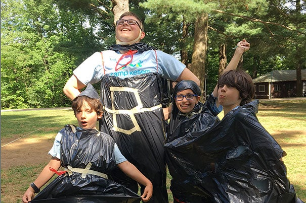 Frankie Hall, a junior concentrating in government, models trash bag designs with young campers.