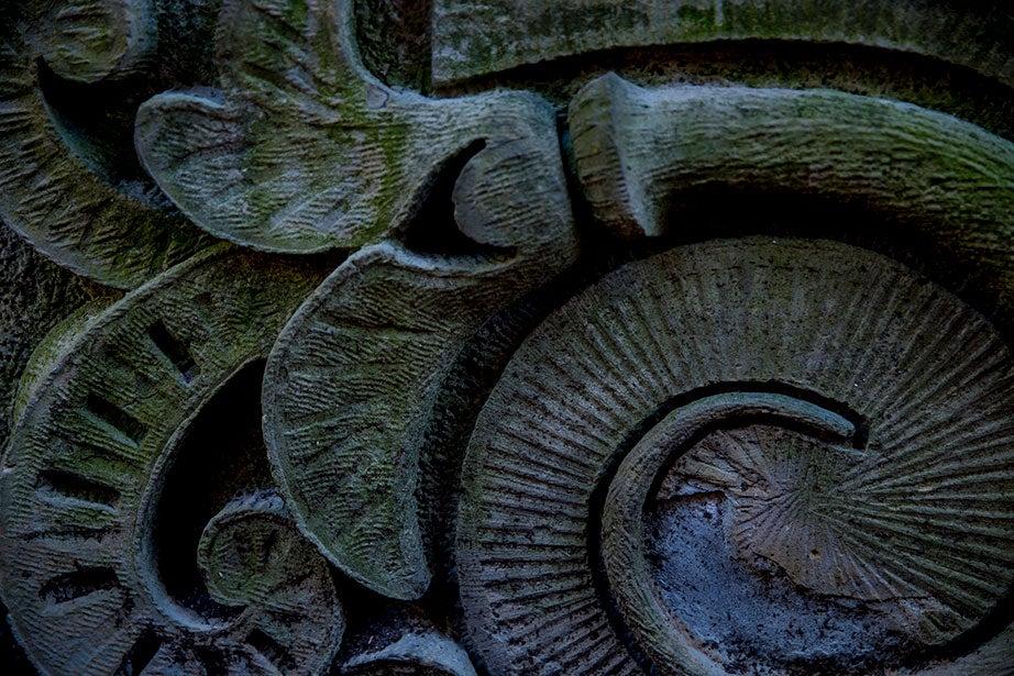Intricate stone carvings loop on a block in a hidden corner.