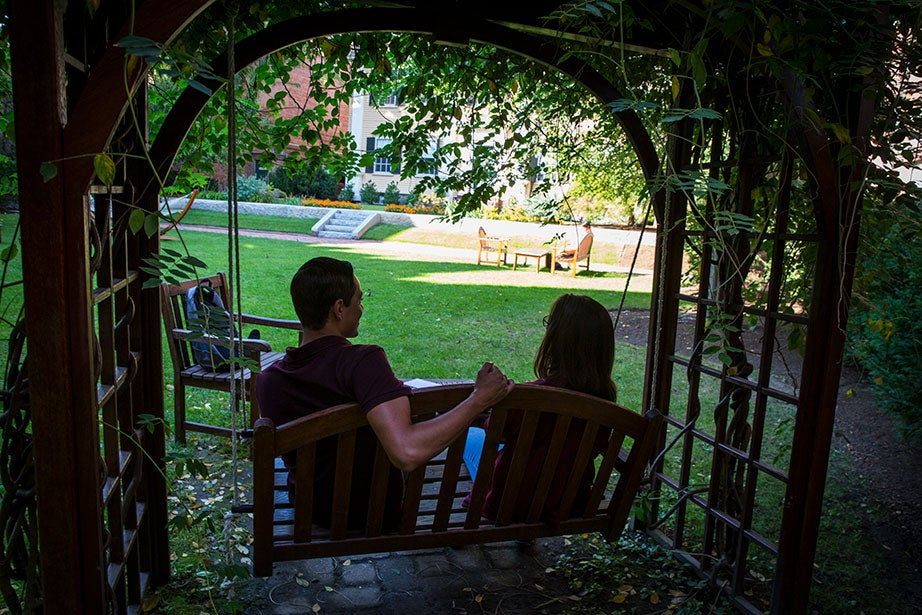 Grace Whitney '20 and Diego Covarrubias '20 talk under a wisteria-covered arbor on a swing in the courtyard.