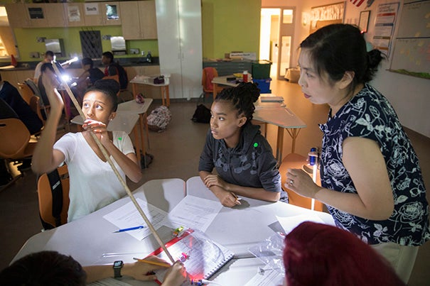 Harvard scientists and Cambridge Public Schools educators are collaborating on a special-thinking program that uses the WorldWide Telescope platform. Putnam Avenue Upper School eighth-graders Liam Mahari (left) and Viviany Barbosa Brito work with project director Patricia Udomprasert during a hands-on lab.