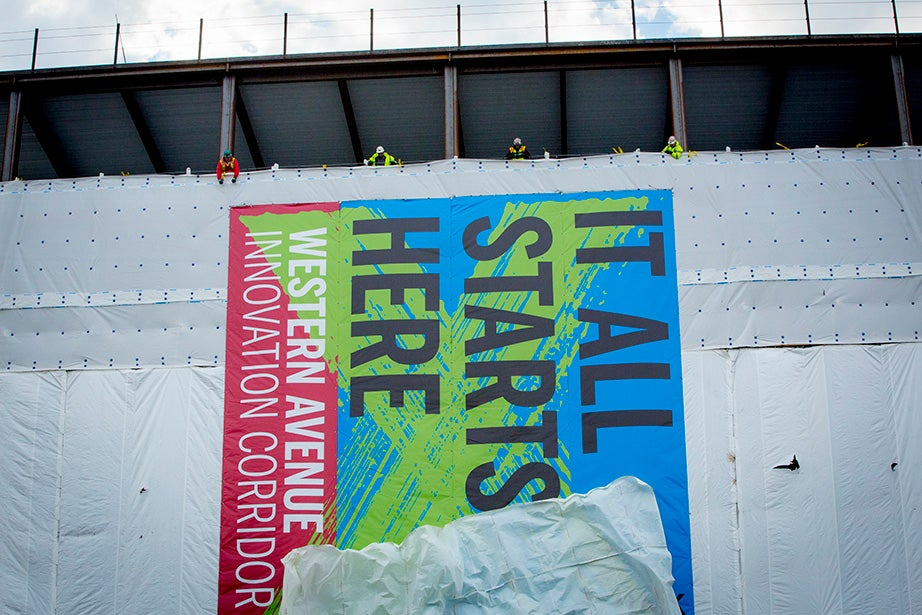 Members of the construction crew reveal a banner facing Western Avenue.