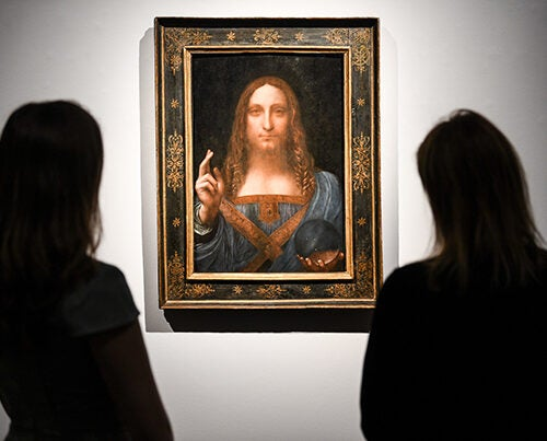 Gallery workers view Leonardo da Vinci's 'Salvator Mundi' painting at Christie's Auction House.