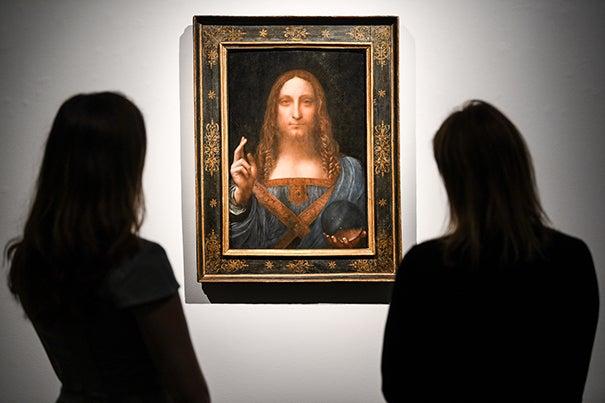 Gallery workers view Leonardo da Vinci's 'Salvator Mundi' painting at Christie's Auction House.