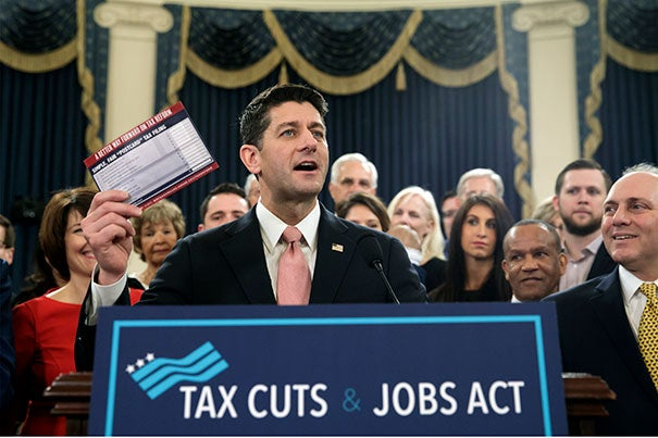 """Speaker of the House Paul Ryan, R-Wis., with House Majority Whip Steve Scalise, R-La., far right, holds a proposed """"postcard tax filing form"""" as they unveil the GOP's far-reaching tax overhaul, the first major revamp of the tax system in three decades, on Capitol Hill in Washington, Thursday, Nov. 2, 2017."""
