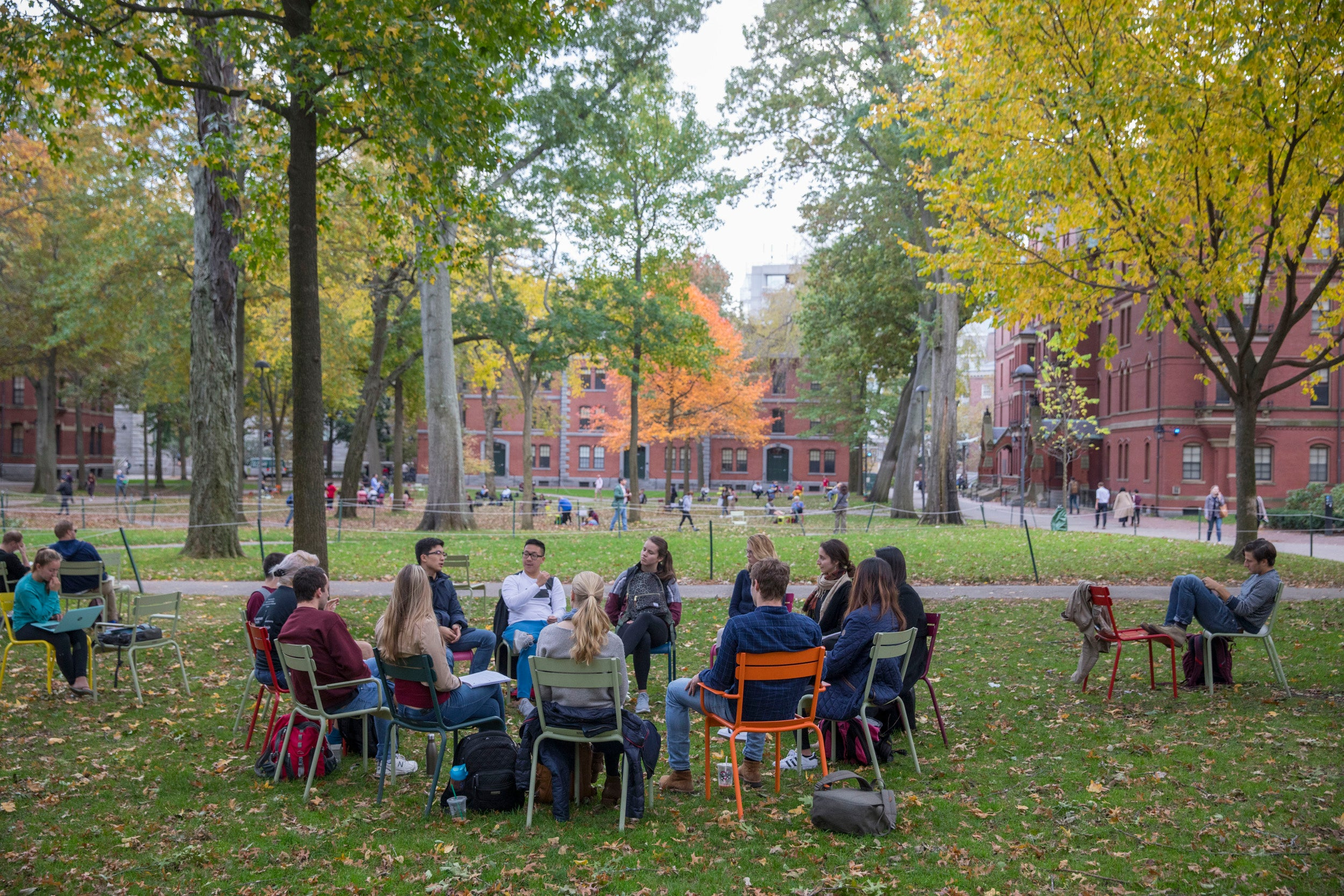 A circle of students sit in chairs in Harvard Yard.