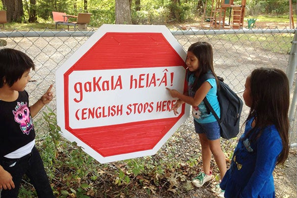 Outside the Yuchi House in Sapulpa, Oklahoma, a student sounds out the words on a stop sign informing students and visitors that English is not to be spoken on the premises.