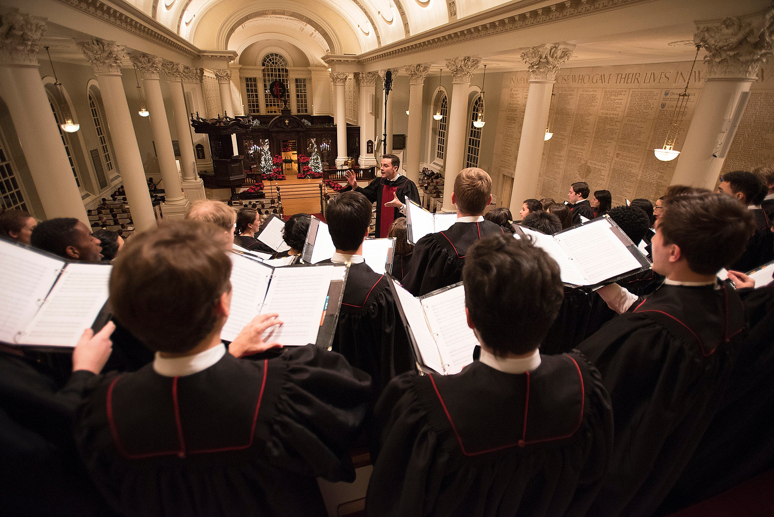 Choirmaster conducts Harvard choir during Christmas service in Memorial Church.
