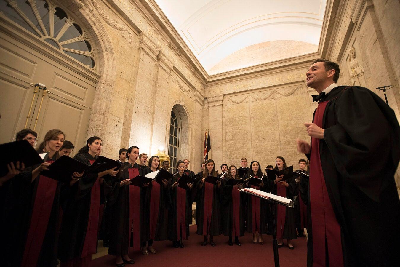 Choir singers ring conductor.