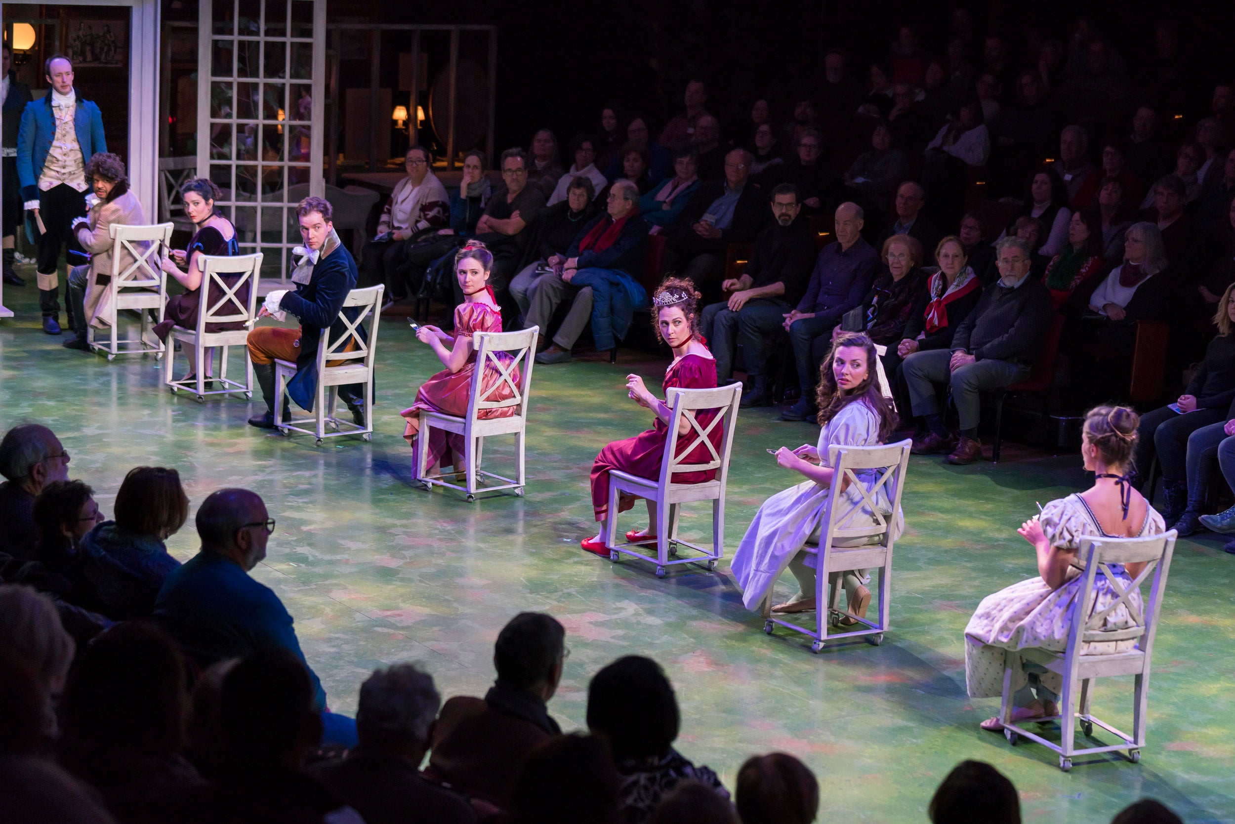 Actors sit in chairs lined up across the stage.