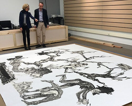 """Harvard Art Museums curators Mary Schneider Enriquez and Edouard Kopp view Kara Walker's """"U.S.A. Idioms"""" at the museums' Somerville Research Center."""