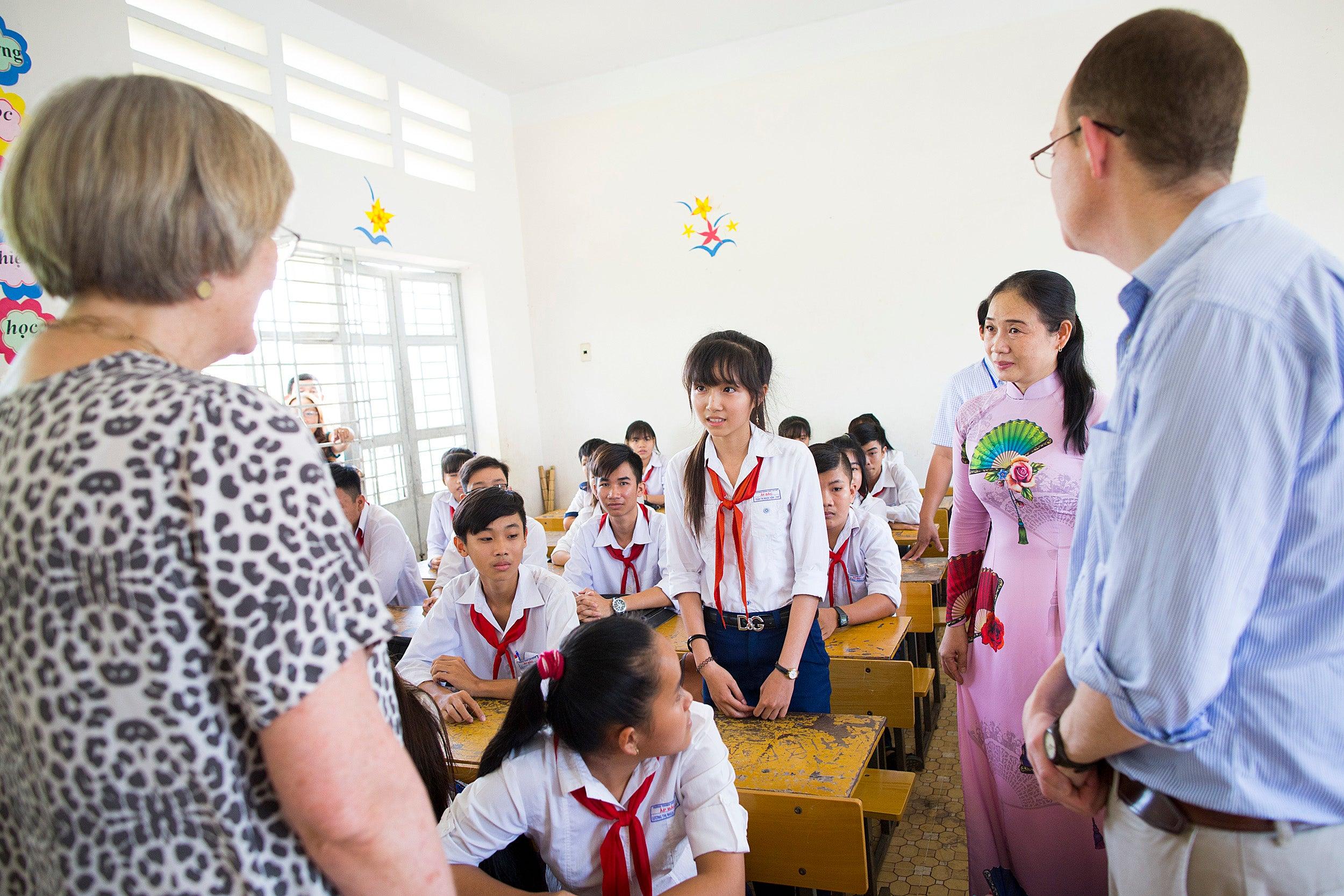 Children in a Vietnamese classroom talk with Harvard President Drew.