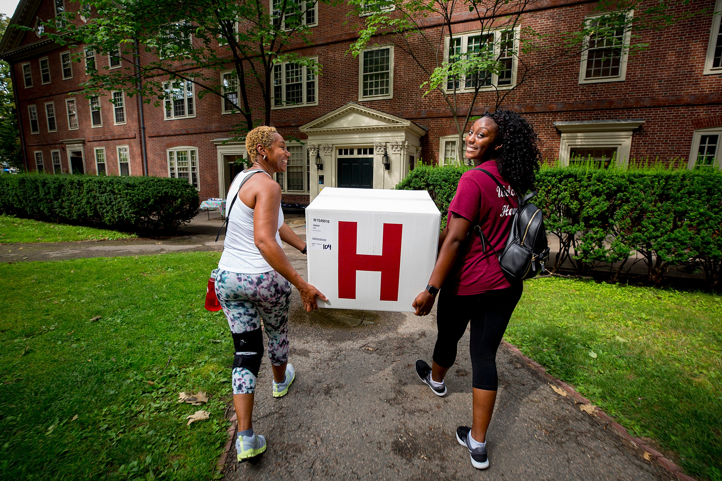 Freshman Leah Smart and her mother, Dee, carry box into Harvard dorm.
