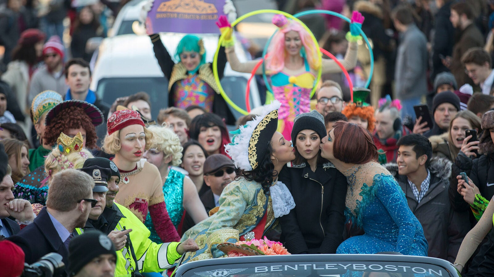 Hasty Pudding Woman of the Year Mila Kunis enjoys her parade through Harvard Square with kisses from Amira Weeks '18 (left) and Jacques Berguig '18.