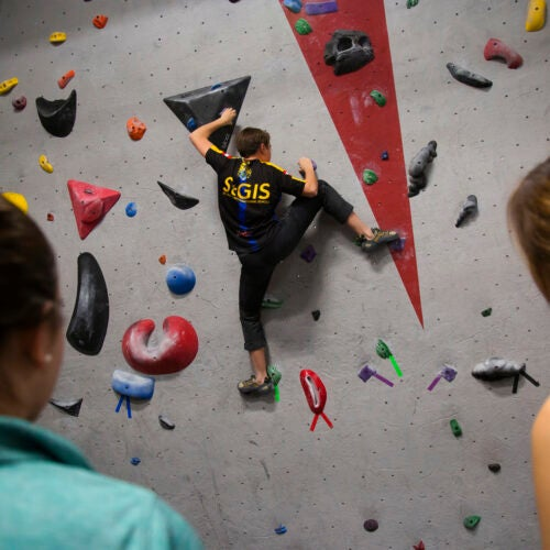 Kami Krista '21 scales Harvard's bouldering wall while members of the Climbing Club look on.